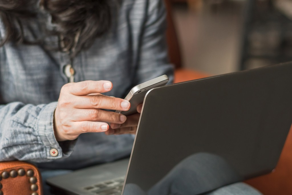 Woman browsing on her phone and laptop