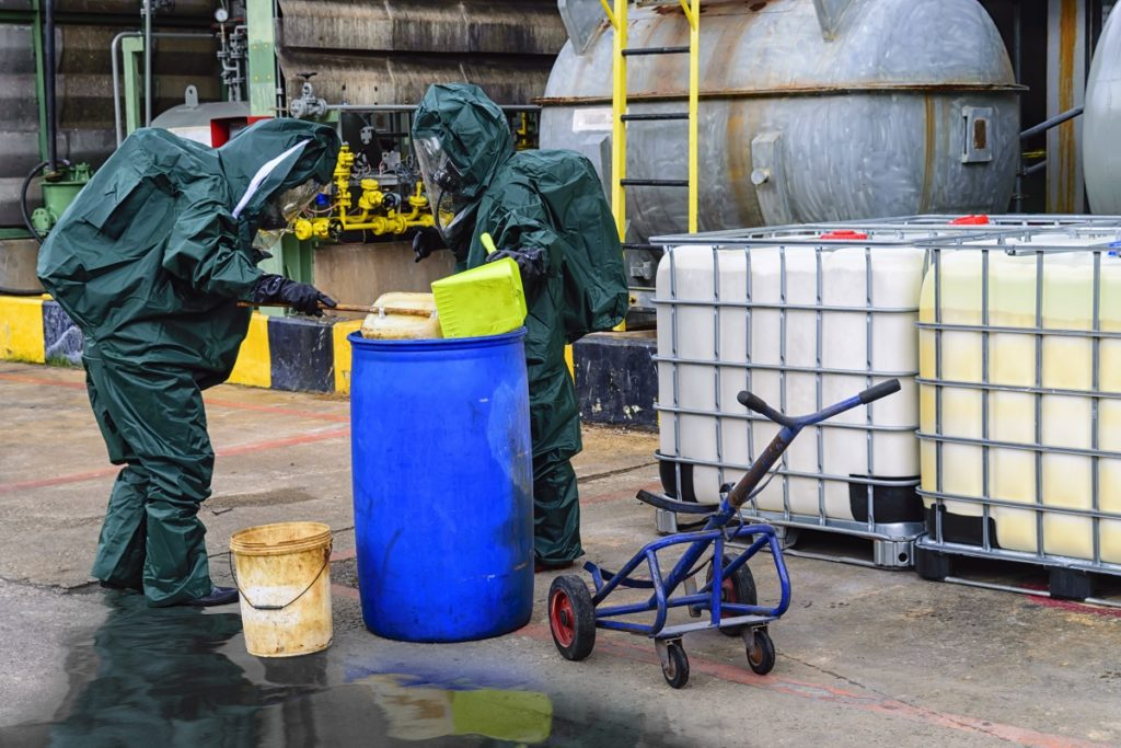 Men checking barrel chemical