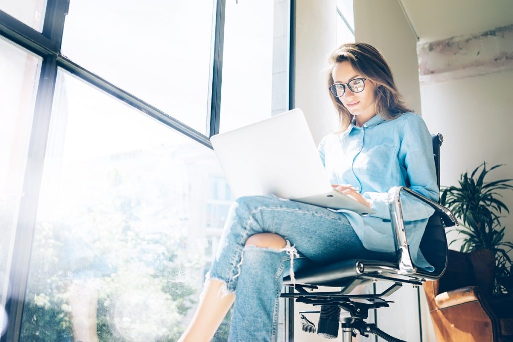 woman writing content on her laptop